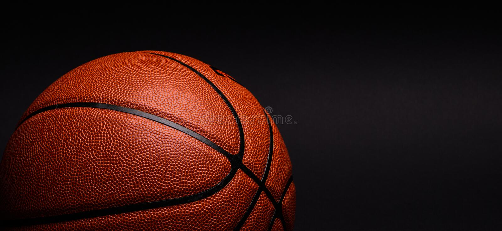 Basketball ball on black background. Game, dark, leather, nba, shadow, sport, texture royalty free stock images