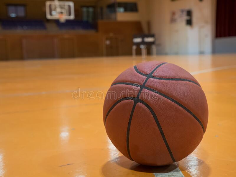 Basketball ball on the court with free throw line. Out of focus basket in the background royalty free stock photo