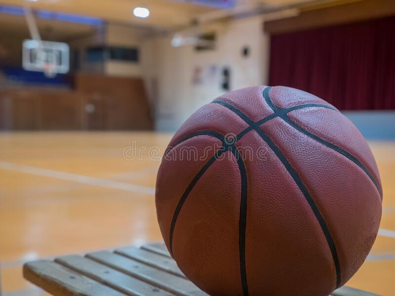 Basketball ball on the court with free throw line, out of focus basket in the background royalty free stock image