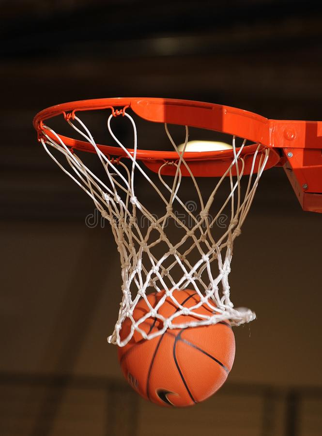 Basketball ball going through the net. royalty free stock images