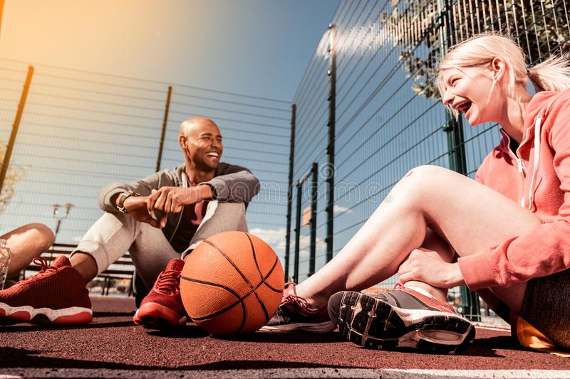 Basketball ball lying near a happy young girl stock photo
