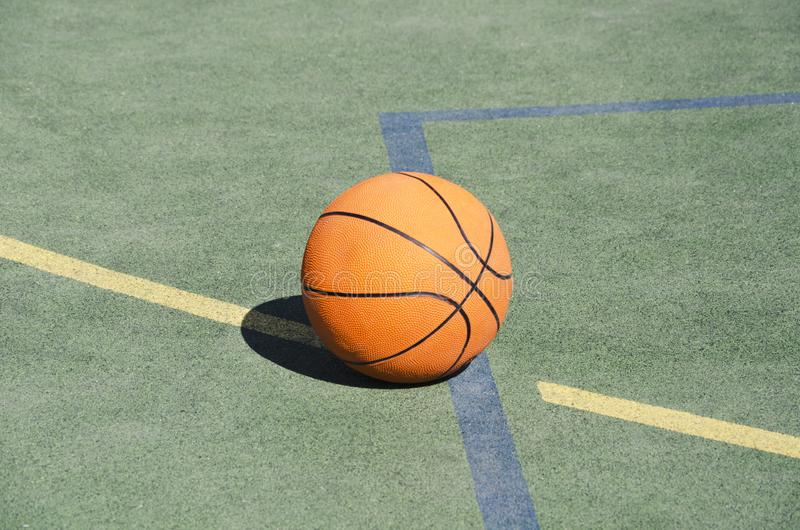 Basketball ball on the rubber sport ground outdoor. Closeup of orange ball on the school playground stock images