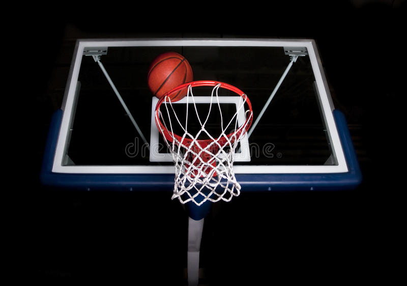 Basketball Basket on Black Background. A basketball basket with a ball going into the hoop on a black background royalty free stock images