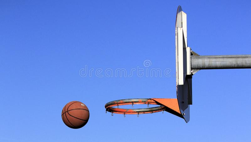 Basketball Being Thrown at the Hoop at an Outdoor Court. One Brown Basketball being thrown at the basketball hoop at an outdoor court on a bright sunny day with royalty free stock photos