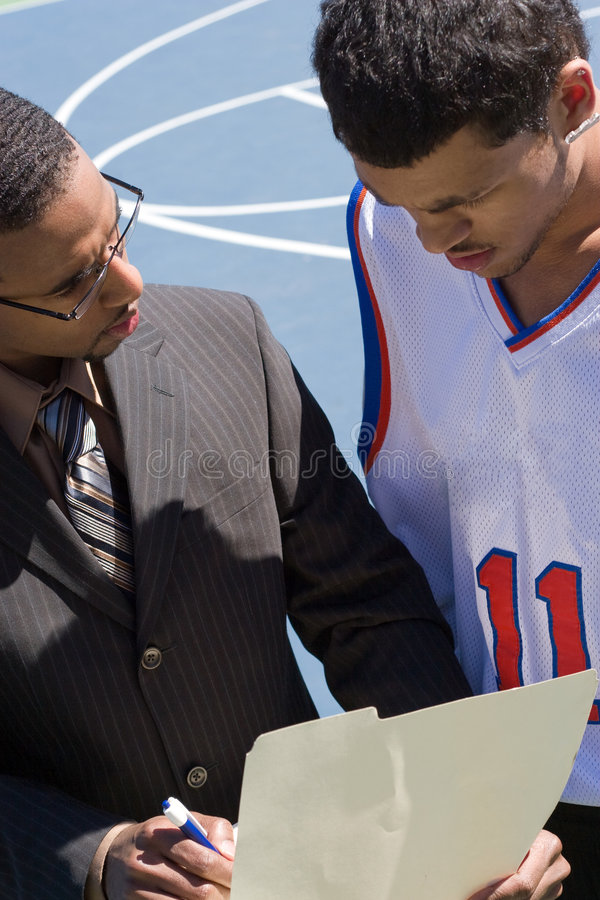 Basketball Coach. A basketball coach in a business suit sharing a play with a player on the team. He could be also be recruiter trying to get him to sign a stock photo