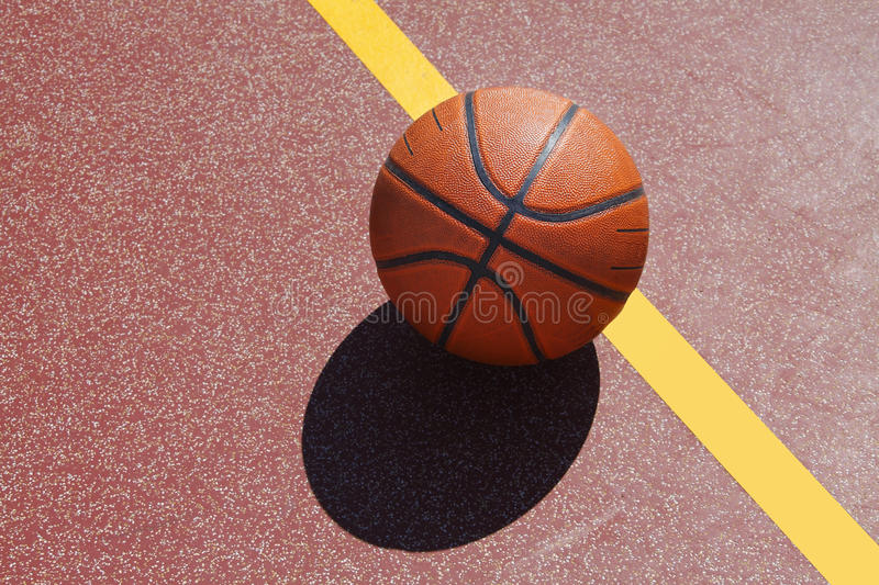 Basketball on court. Orange basketball with shadow on sports court royalty free stock photo