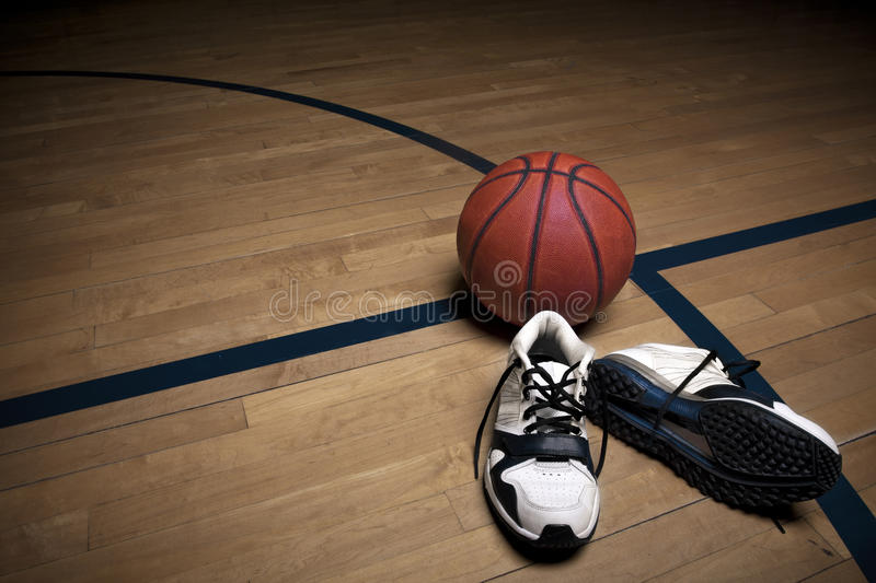 Basketball Court. A basketball court floor with a ball and athletic shoes as the focal point royalty free stock image