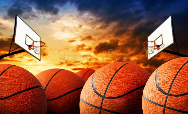 Basketball court and balls. Balls on basketball court with hoops in background, selective focus stock photography