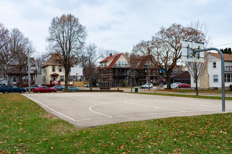 Basketball Court in the Midwest during a Cold Day. A simple basketball court at a Midwest park surrounded by homes in Madison Wisconsin stock image