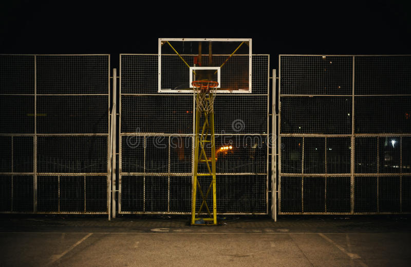 The Basketball Court. During night, view on basketball hoop and fence royalty free stock photography
