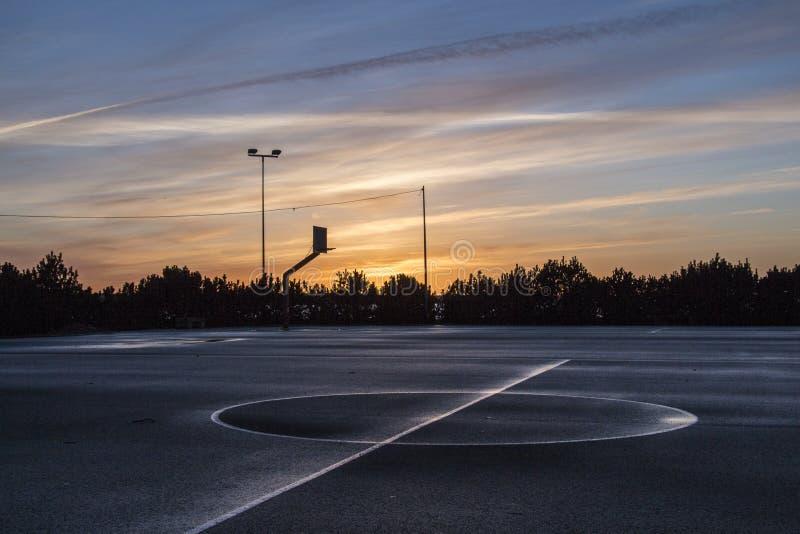 Basketball court in sunset after rain. Wet asphalt basketball court. stock photo
