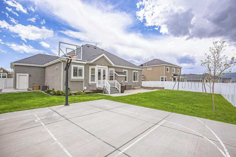 Basketball court and swings on the spacious yard of a single storey family home. Overhead is a picturesque vibrant blue sky with fluffy clouds royalty free stock photography
