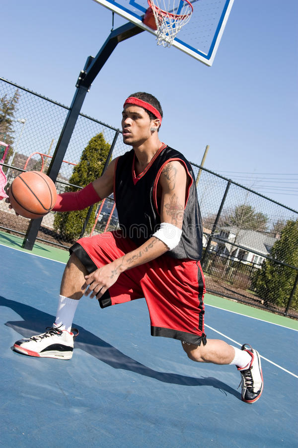 Basketball Crossover Dribble. A young basketball player demonstrating his crossover dribble and ball handling abilities royalty free stock images