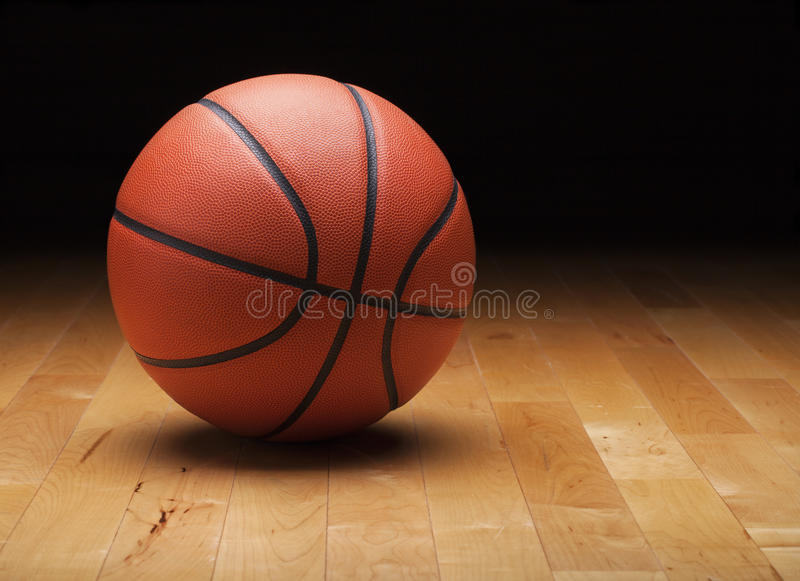 Basketball with dark background on wood gym floor. A basketball with a dark background on a hardwood gym floor royalty free stock photos