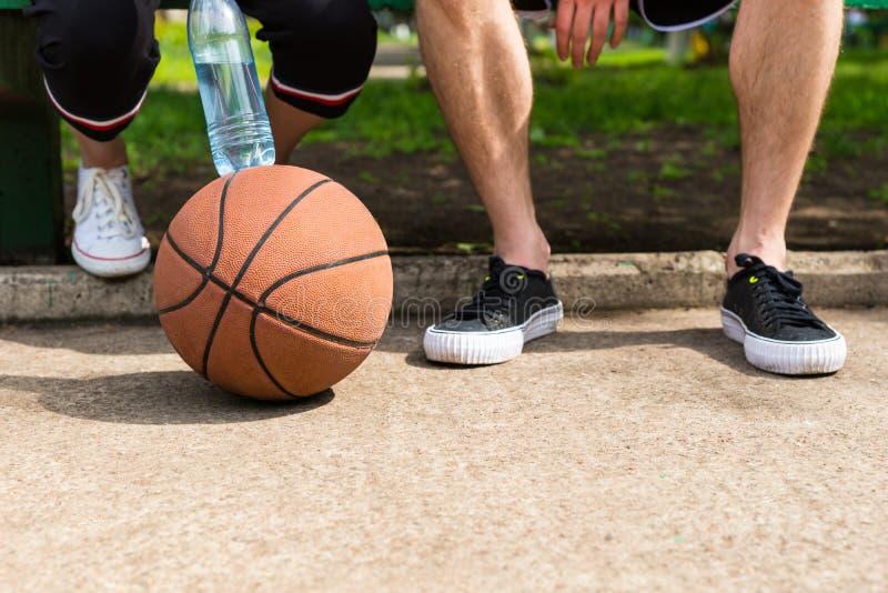 Basketball an den Füßen Paaren, die auf Park-Bank sitzen lizenzfreie stockfotos