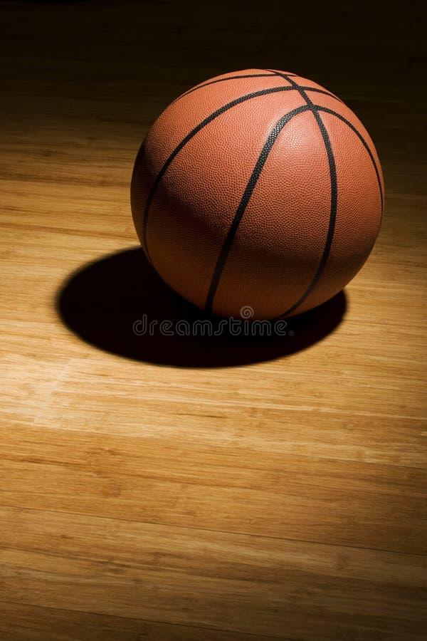 Basketball, der auf hölzernem Fußboden sitzt lizenzfreies stockfoto