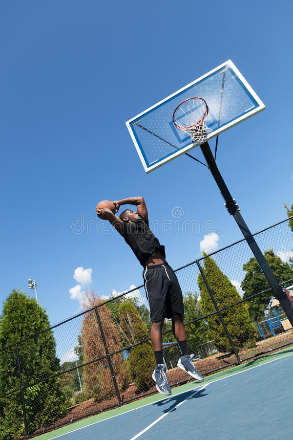 Basketball Dunk from Below. Young basketball player driving to the hoop for a high flying slam dunk. Shallow depth of field royalty free stock photos