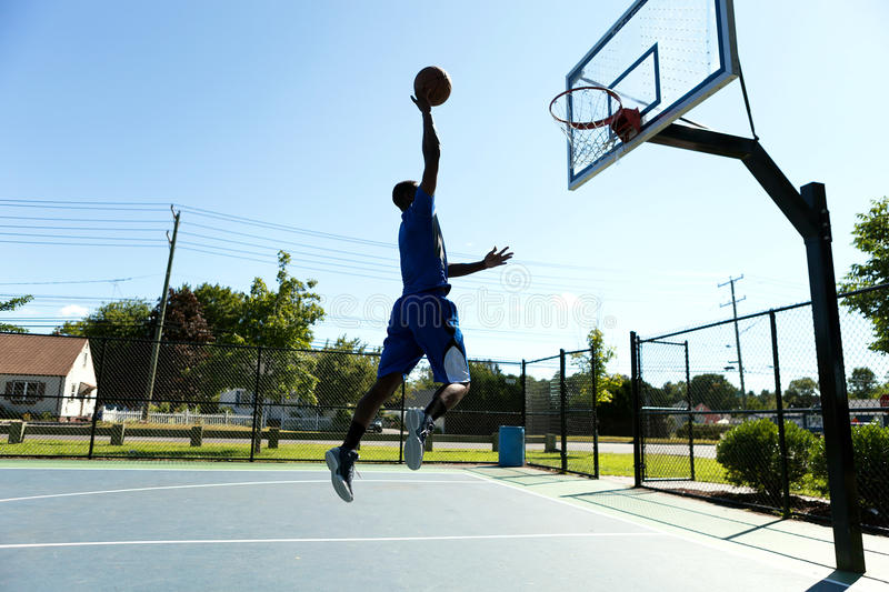 Basketball Dunk Outdoors. Young basketball player driving to the hoop for a high flying slam dunk royalty free stock photo
