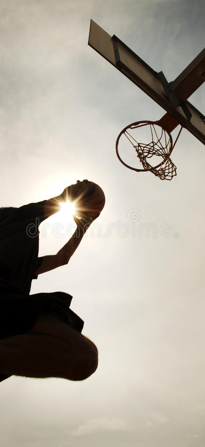 Basketball dunk silhouette. Dunk silhouette of a basketball player in a backlight cloudy day royalty free stock images