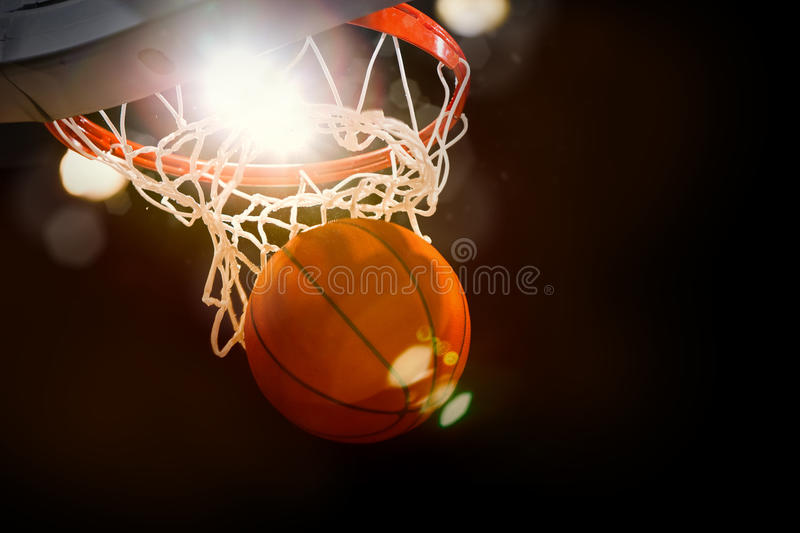 Basketball Game Action. Basketball going through the basket with bright arena lights shining down stock photography