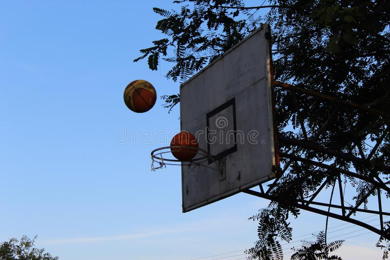 Two basketball balls being thrown into the basket at the same time royalty free stock photos