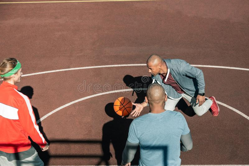 Top view of pleasant young men playing basketball stock image