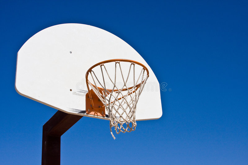 Basketball Goal with backboard net and rim. Basketball Goalpost with backboard and a rim and hoop and net and blue sky in the background royalty free stock photo