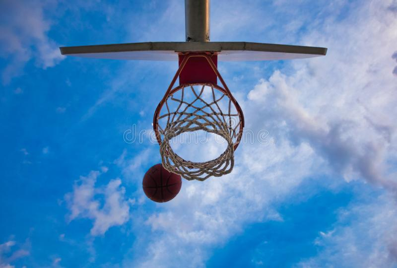 A Basketball going into a Basketball Hoop royalty free stock image