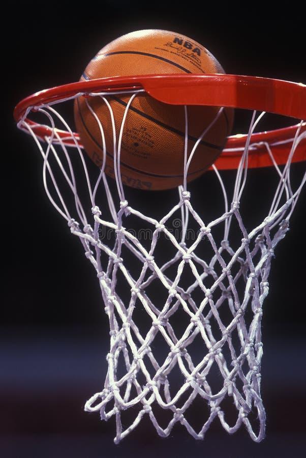 Basketball Going Thru A Basketball hoop. NBA basketball game with a ball going thru the hoop and net for basket royalty free stock images