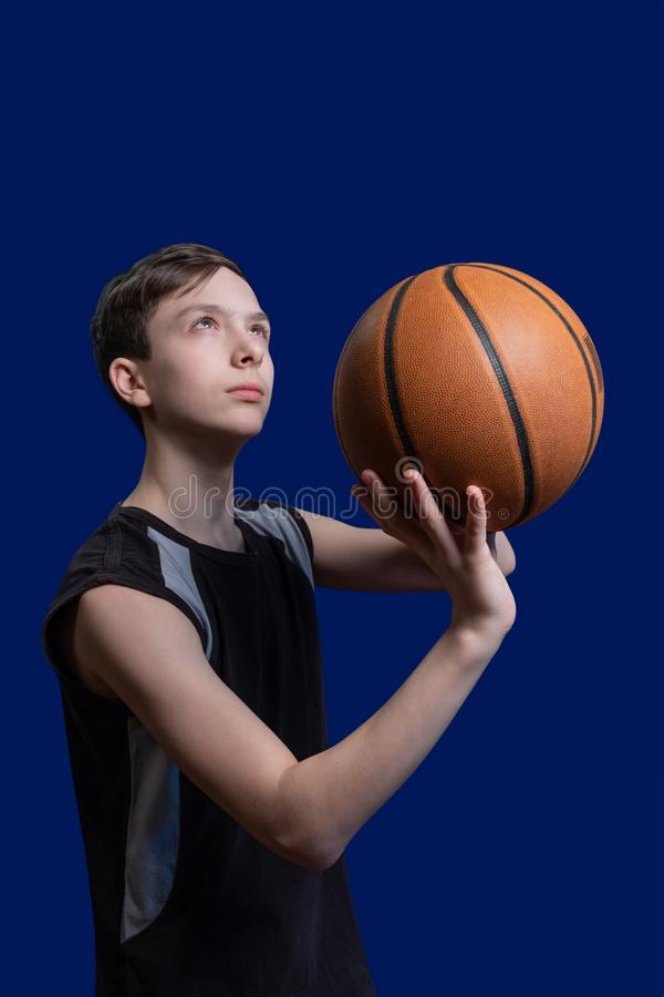 Basketball. The guy in the black T-shirt is preparing to throw the ball. Blue background. Teen basketball player. Basketball. The guy in the black T-shirt is stock photo