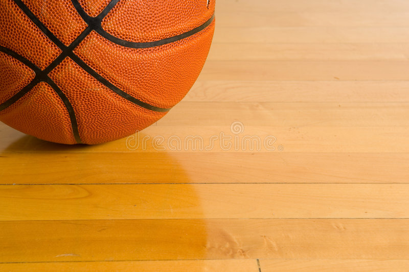 Basketball on gym floor. Leather basketball on wooden gym floor stock images