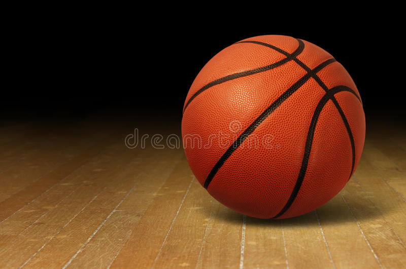 Basketball On Wood Court. Basketball on a hardwood court floor as a sports and fitness symbol of a team leisure activity playing with a leather ball dribbling royalty free stock image