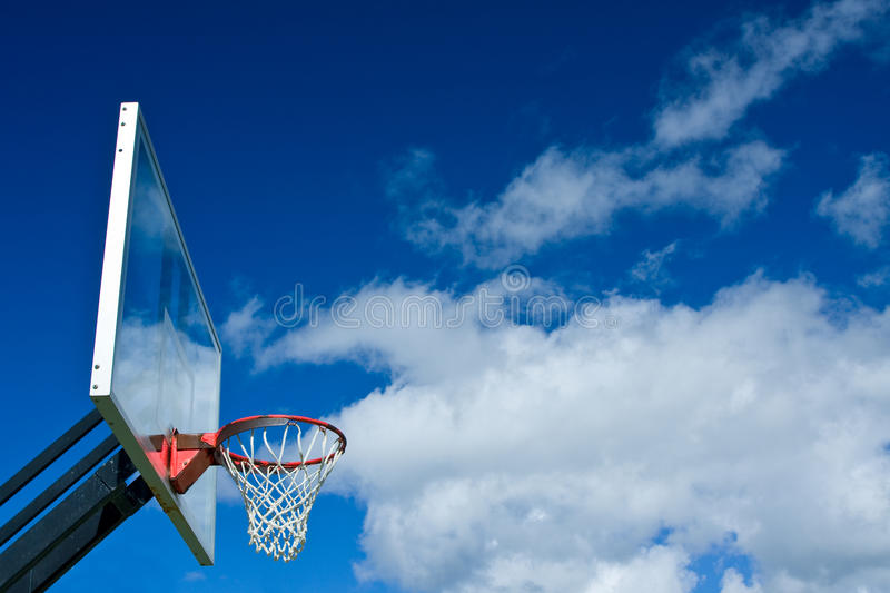 Basketball hoop. Outdoor basketball hoop with blue sky and clouds stock image