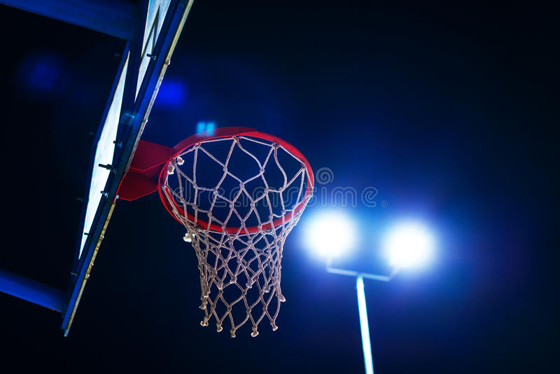 Basketball hoop on outdoor court at night. Basketball hoop on outdoor sport court at night with lens flare stock image