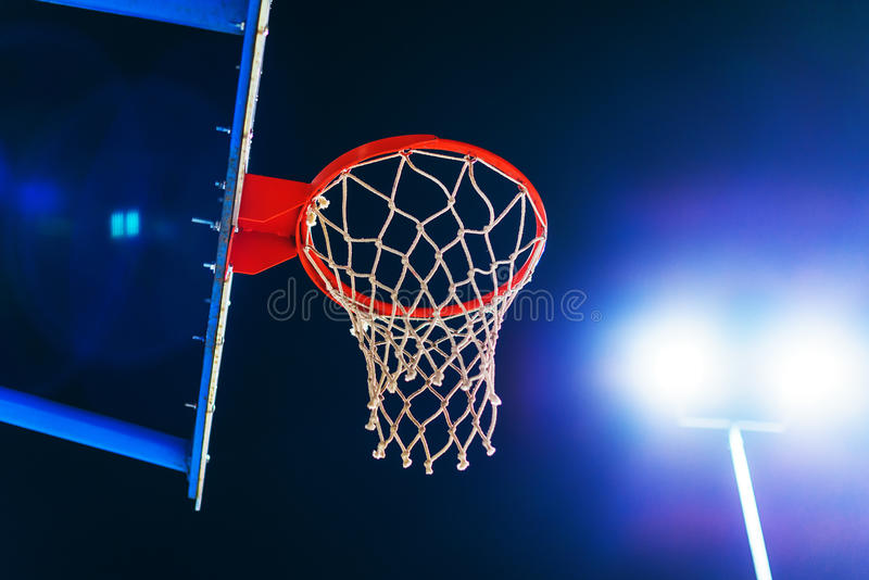 Basketball hoop on outdoor court at night. Basketball hoop on outdoor sport court at night with lens flare stock images