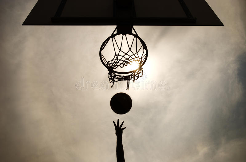 Basketball hoop shot. An arm and hand in silhouette shooting a basketball through a hoop stock photography