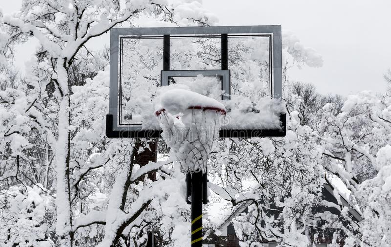 Basketball hoop with snow in it after a storm. A basketball hoop is full of snow with trees covered in snow in the background after a spring snow storm in Long stock photography