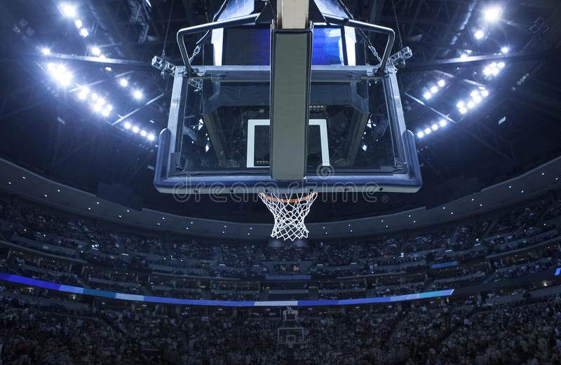 Basketball Hoop in a sports arena. Brightly lit Basketball backboard in a large sports arena. Rim and net in focus stock photography