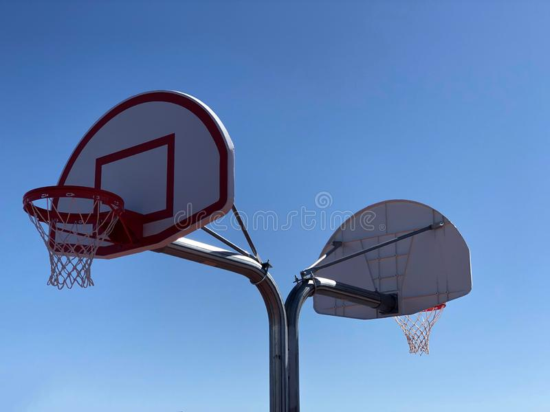 Basketball Hoops. Basketball hoop with net on a basketball court with a bright blue sky in Arizona royalty free stock image