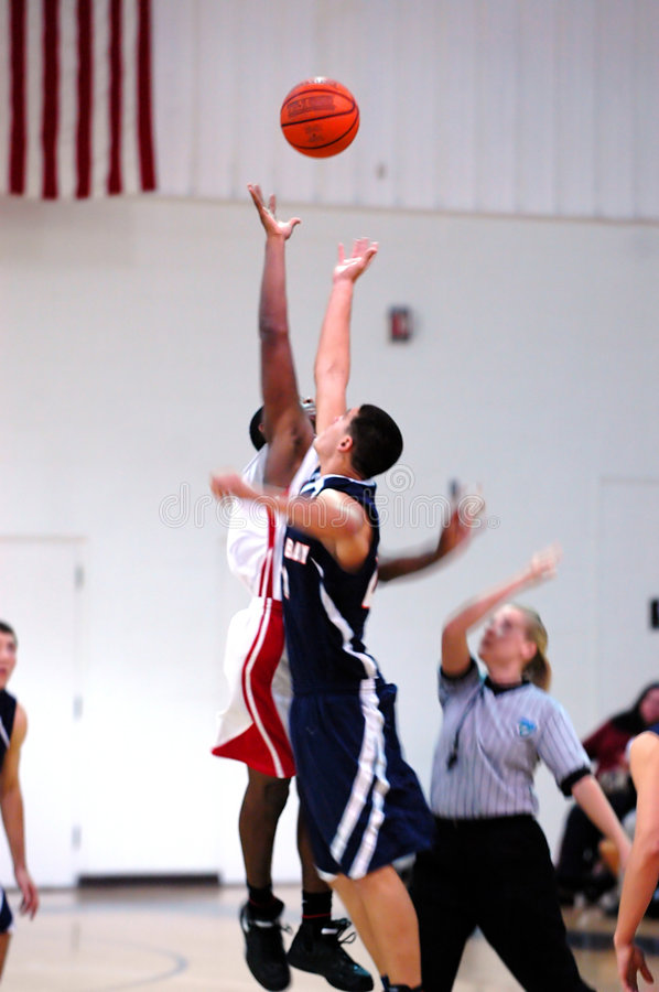Basketball jump blur. Action during the start of a high school basketball game (motion blur stock photo