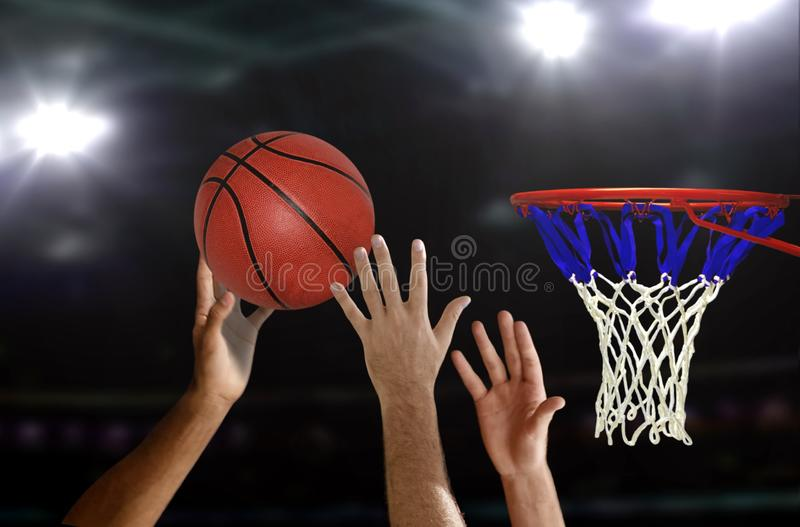Basketball jump shot to the hoop. With stadium bright spotlights stock images