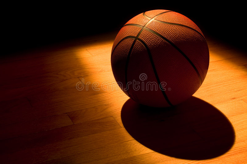 Basketball in the light. Basketball left on the court after a game stock photography
