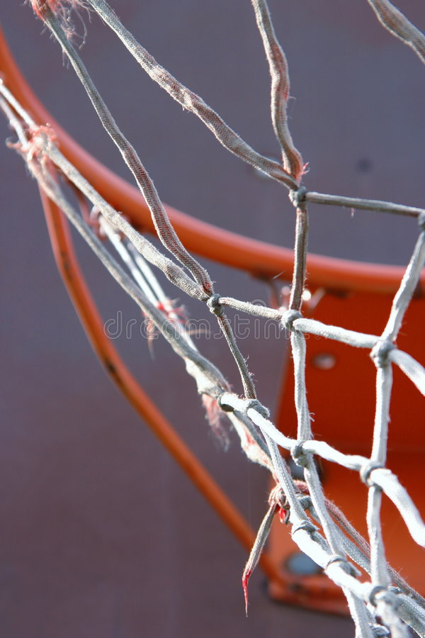 Basketball net. A basketball hoop with a rugged and old net stock photography