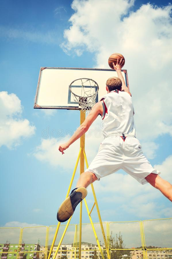 Basketball player in action flying high and scoring royalty free stock photography