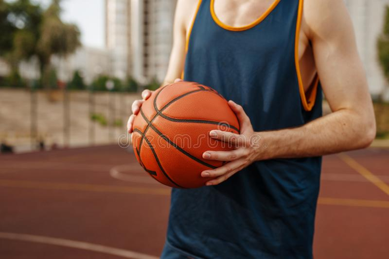 Basketball player aiming for throw, outdoor court. Basketball player aiming for the throw on outdoor court. Male athlete in sportswear holds ball on streetball royalty free stock photo