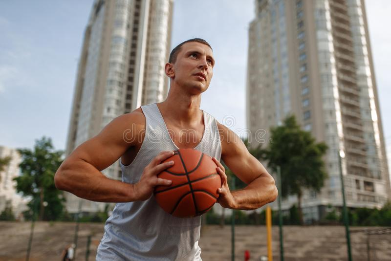 Basketball player aiming for throw, outdoor court. Basketball player aiming for the throw on outdoor court. Male athlete in sportswear holds ball on streetball royalty free stock image