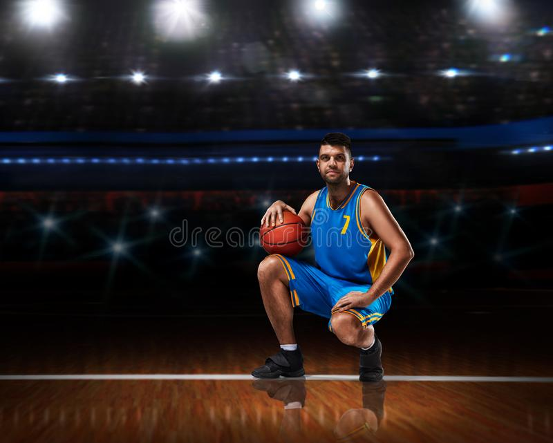 Basketball player in blue uniform sitting on basketball court royalty free stock photography