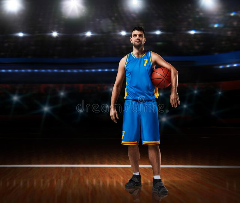 Basketball player in blue uniform standing on basketball court royalty free stock photography