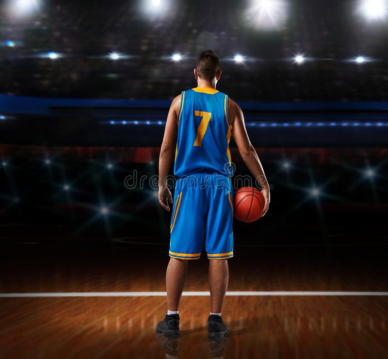 Basketball player in blue uniform standing on basketball court royalty free stock images