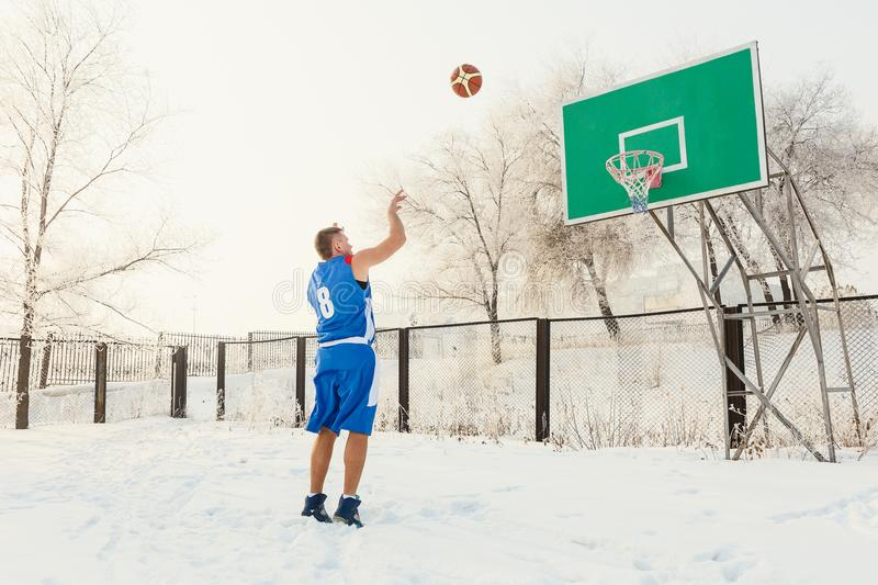 Basketball player in blue uniform throwing a basketball ball into the basket on a street basketball court in the winter royalty free stock photo